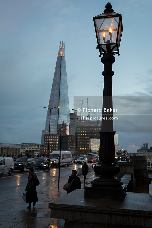With the Shard in the background, pedestrians and traffic on London Bridge during the evening rush-hour, on 7th November 2018, in London, England.