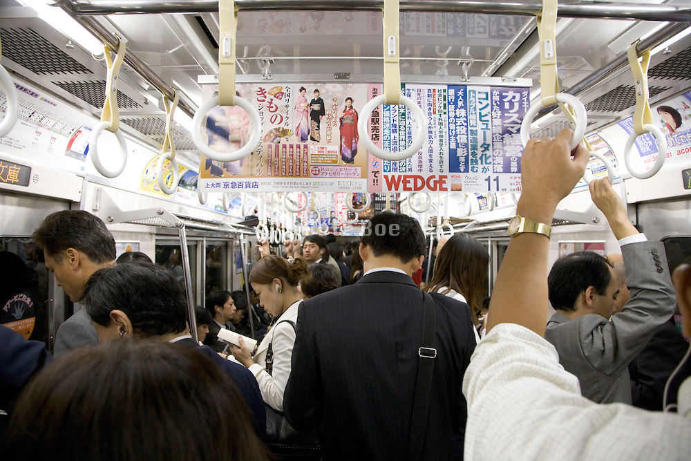 straphangers in a crowded train during rush hour Tokyo Japan