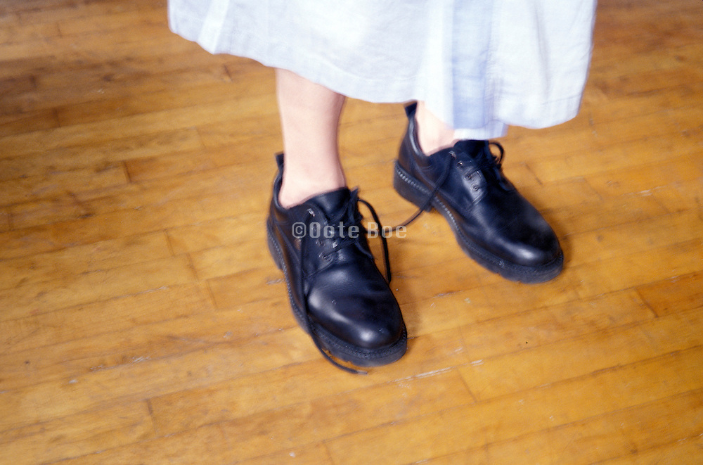 person wearing black shoes on wooden floor