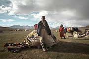 Tella Bu, one of the daughter of the late Khan, and her husband Daryo Boi, after unloading the yaks, piles up all his worldy goods at the new summer camp. This represents everything he owns...Moving with the Khan (chief) family. The couple of Tella Bu and Daryo Boi family arrive from the Qyzyl Qorum camp to the summer camp of Kara Jylga, on the south side of the wide Little Pamir plateau...Trekking through the high altitude plateau of the Little Pamir mountains (average 4200 meters) , where the Afghan Kyrgyz community live all year, on the borders of China, Tajikistan and Pakistan.