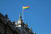 Rainbow flag flying on the rooftop of the Cabinet Office on Whitehall on 26th February 2020 in London, United Kingdom.  The rainbow flag, commonly the gay pride flag and sometimes the LGBT pride flag, is a symbol of lesbian, gay, bisexual, and transgender LGBT pride and LGBT social movements. It has been in use since the 1970s.
