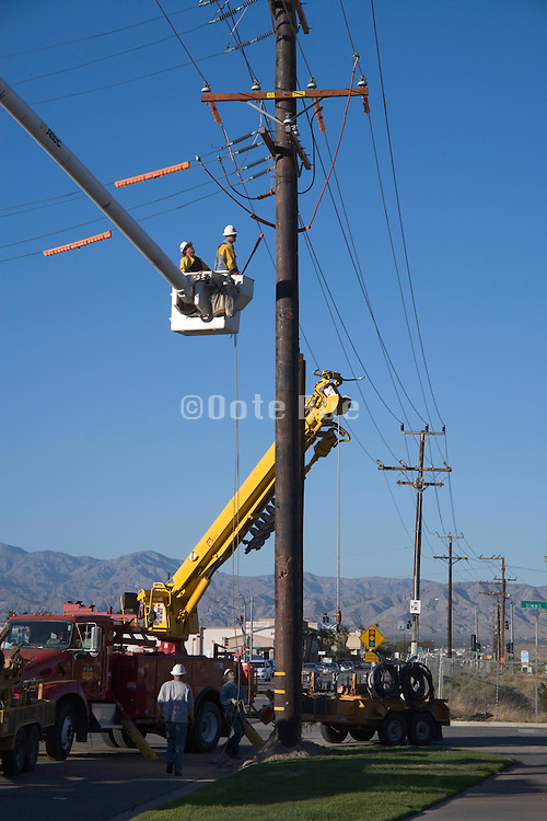 hoisted construction workers working on above ground placed electrical wires USA