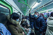 Passengers some of them wearing face protective surgical masks to curb the spread of coronavirus pandemic outbreak, hold on to the handle during a train ride from Republic Square in Armenia's capital city Yerevan metro on Friday, Jan 29, 2021. Yerevan metro has one line and operates 10 stations. The frequency of the trains during the busy hours is every five minutes, and the other hours, 15 minutes. (Photo/ Vudi Xhymshiti)