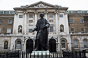The statue of Sir Thomas Guy stands outside the historical entrance of Guys hospital, on 9th June 2020, in London, England. Thomas Guy 1644 – 1724 was British bookseller, speculator and founder of Guys Hospital, London whose links to the global slave trade is now a controversial aspect of this businessman by anti-slavery activists and more recently, Black Lives Matter protesters. His wealth came through shares in the South Sea Company whose main business was in the selling of slaves from Africa to the Spanish colonies. In 1720 he successfully sold his stock of the company for approx £400 million at todays prices and amassed a large fortune, opening the Guys Hospital  in 1725 which today serves as one of  the capitals major NHS healthcare centres. In the aftermath of the George Floyd protests in the US and UK Black Lives Matter groups who are calling for the removal of statues and street names with links to the slave trade, Guys and other statues of British slavery owners and profiteers, have become a focus of impassioned protest.