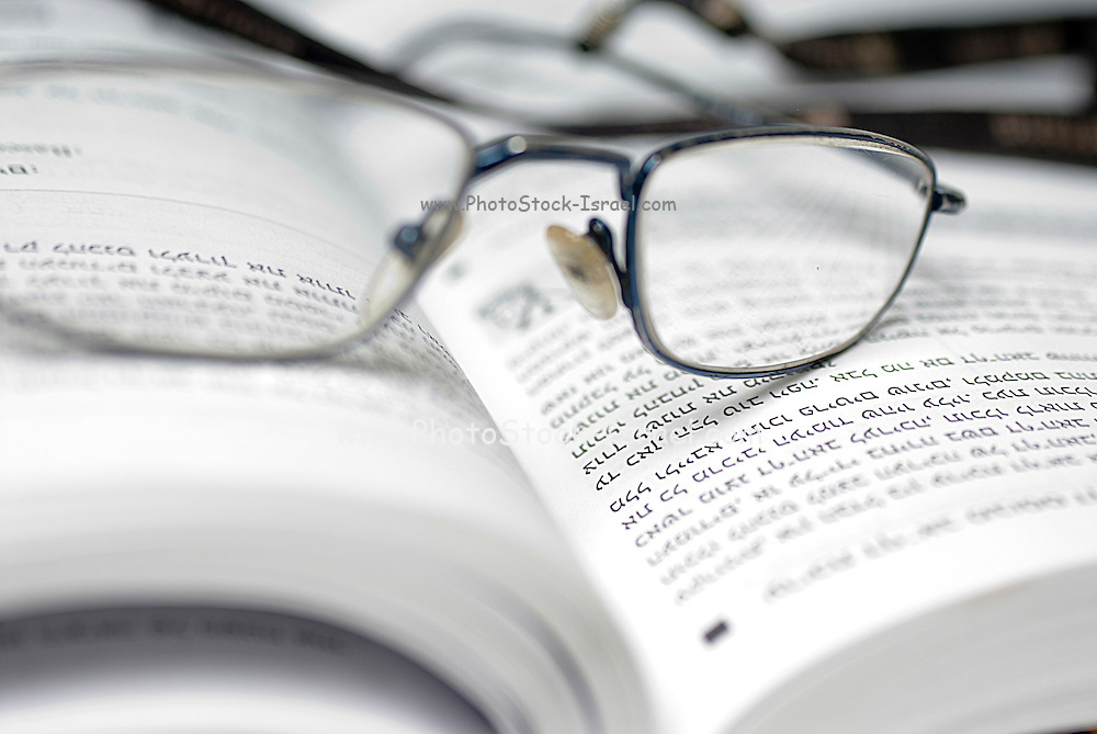 reading glasses on an open book with text in Hebrew
