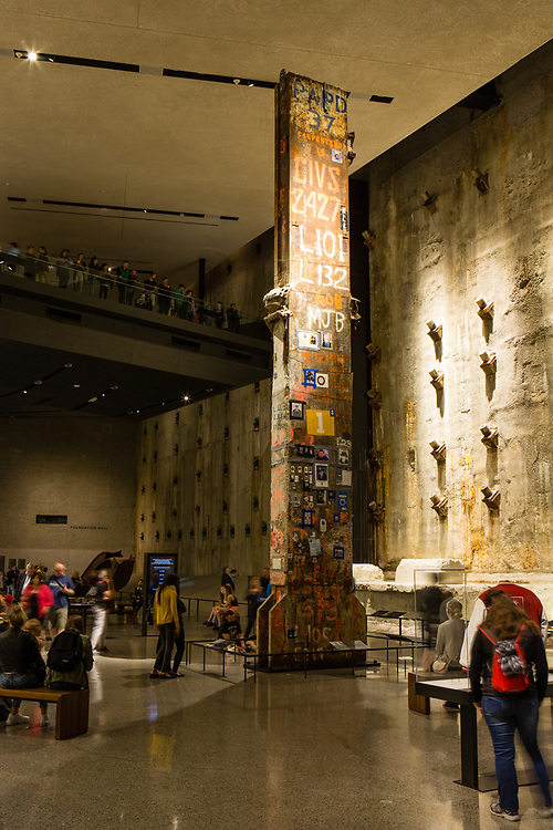 A girder from the Twin Towers stands before the original slurry wall in the 9/11 Memorial.