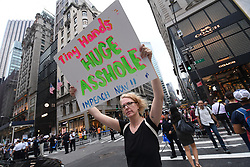 A protester holds a sign up during near Trump Tower for the second day of an Anti-Trump rally during President Donald Trump's first stay in New York City since taking office, New York, NY, on August 15, 2017. (Photo by Anthony Behar)