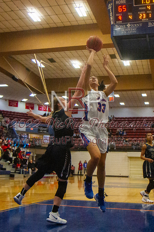 Moore's Raychael Harjo raises above Southmoore's Torie Simon for a layup during the game on Tuesday, December 18, 2018 at Moore High School.