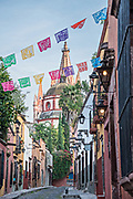 Domes and spires of the Parroquia San Miguel Arcangel church seen through paper banners called papel picado on Aldama Street in the historic district of San Miguel de Allende, Mexico.