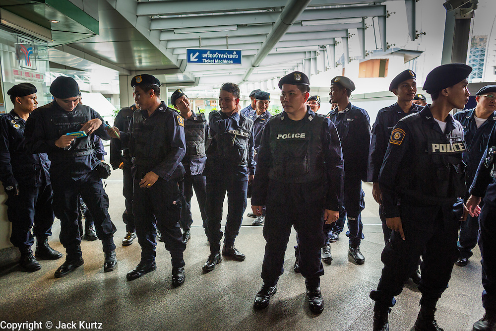 """01 JUNE 2014 - BANGKOK, THAILAND: Thai police line up to remove protestors from Terminal 21 shopping mall in Bangkok after a flash mob protested against the coup in the mall. The Thai army seized power in a coup that unseated a democratically elected government on May 22. Since then there have been sporadic protests against the coup. The protests Sunday were the largest in several days and seemed to be spontaneous """"flash mobs"""" that appeared at shopping centers in Bangkok and then broke up when soldiers arrived. Protest against the coup is illegal and the junta has threatened to arrest anyone who protests the coup. There was a massive security operation in Bangkok Sunday that shut down several shopping areas to prevent the protests but protestors went to malls that had no military presence.    PHOTO BY JACK KURTZ"""