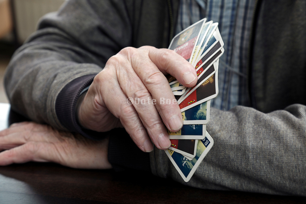 hands of an 89 year man holding cards