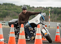 Laconia Patrolman Robb Sedgley maneuvers his way around the cones during the Police Motorcycle Driving Course at the Laconia Airport Wednesday morning.  (Karen Bobotas/for the Laconia Daily Sun)