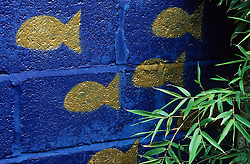 Gold fish stencilled on to blue wall with bamboo - Phyllostachys aurea