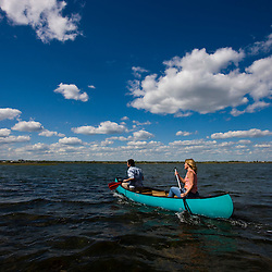 A couple paddles a canoe on the salt marsh side of Long Beach in Stratford, Connecticut.  This body of water is known as Lewis Gut and is adjacent to the Great Meadows Unit of McKinney National Wildlife Refuge.