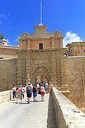 Tourists walking over moat bridge through entrance gateway of medieval city of Mdina, Malta