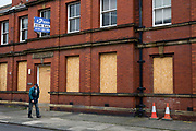 A man walks past a boarded up and closed down magistrates court, Whitley Bay,  Northumberland. UK.