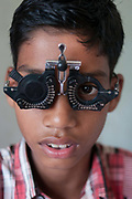 India. Orissa. Village eye camp at Fatak, near Sundergarh. September 2012. A boy's eyes are tested to see what strength glasses he needs.
