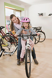 Woman and girl with mountain bike, smiling