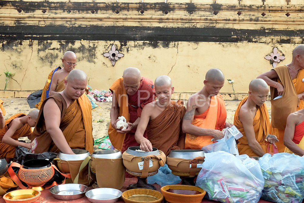 """Buddhist monks collecting alms at the That Luang festival, Vientiane, Lao PDR. Pha That Luang is the national symbol and most important religious monument of Laos. Vientiane's most important Theravada Buddhist festival, """"Boun That Luang"""", is held here for three days during the full moon of the twelfth lunar month (November). Monks and laypeople from all over Laos congregate to celebrate the occasion with three days of religious ceremony followed by a week of festivities, day and night. The procession of laypeople begins at Wat Si Muang in the city centre and proceeds to Pha That Luang to make offerings to the monks in order to accumulate merit for rebirth into a better life. The religious part concludes as laypeople, carrying incense and candles as offerings, circumambulate Pha That Luang three times in honor of Buddha."""