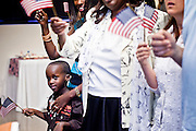 "June 21, 2010 - PHOENIX, AZ: The child of a new citizen sings ""God Bless the USA"" during a naturalization ceremony for former refugees at the International Rescue Committee offices in Phoenix, AZ, Monday, June 21. World Refugee Day was Sunday, June 20; the IRC and US Citizenship and Immigration Services offices  marked the day by holding a naturalization ceremony for 10 people who came to the US as refugees.  Photo by Jack Kurtz"