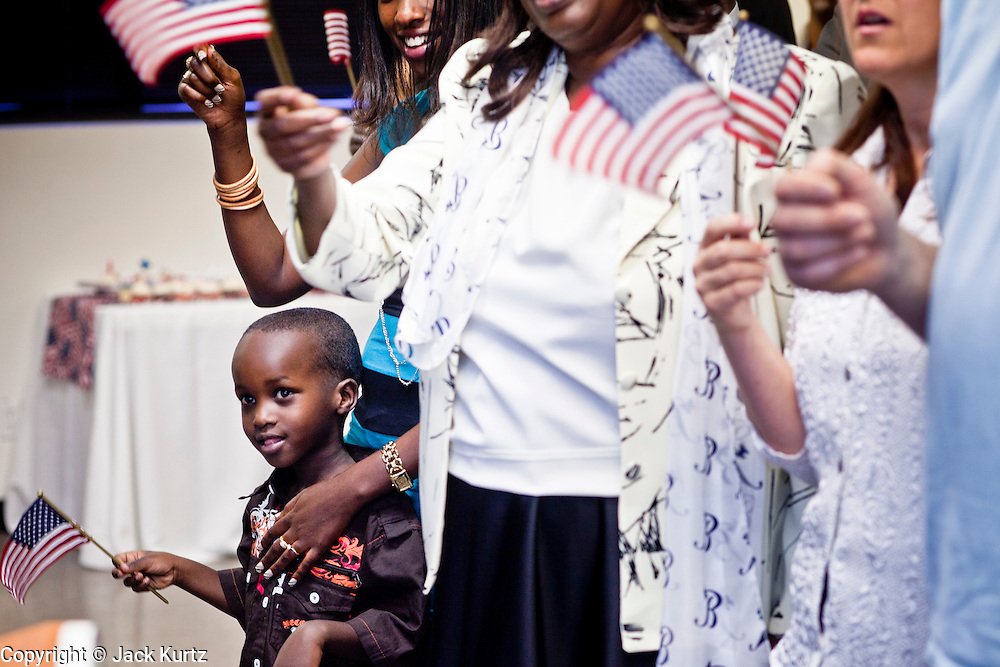 """June 21, 2010 - PHOENIX, AZ: The child of a new citizen sings """"God Bless the USA"""" during a naturalization ceremony for former refugees at the International Rescue Committee offices in Phoenix, AZ, Monday, June 21. World Refugee Day was Sunday, June 20; the IRC and US Citizenship and Immigration Services offices  marked the day by holding a naturalization ceremony for 10 people who came to the US as refugees.  Photo by Jack Kurtz"""