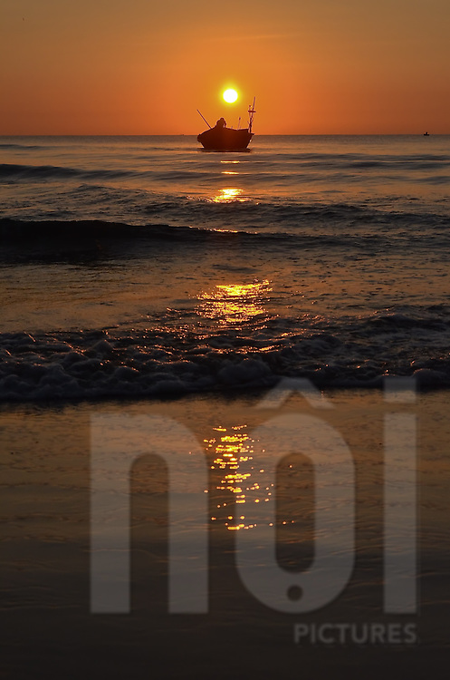 Early morning on a part of China beach in Danang. Silhouette of a fisherman working on his boat while the sun is rising. The light is orange and there is a sun reflection on the waves coming onto the beach.