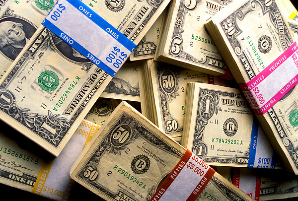 Stock photo of piles of paper currency in different denominations