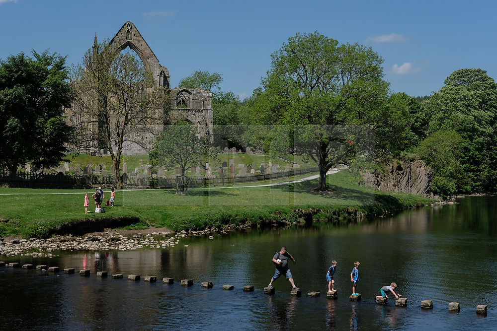 © Licensed to London News Pictures. 26/05/2017. Ilkley, UK. People enjoy the hot temperatures and sunshine aide the River Wharfe at Bolton Abbey in North Yorkshire. Forecasters are predicting the temperatures to rise further still over the bank holiday weekend. Photo credit : Ian Hinchliffe/LNP