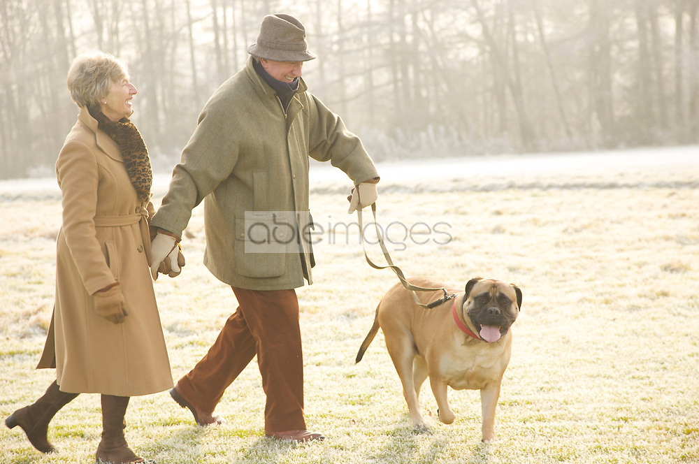 Portrait of a mature couple walking with a dog in the park smiling and laughing