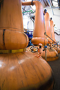 Copper stills for whisky process in traditional Still House part of Visitor Centre visitors tour at Tobermory Distillery, Isle of Mull in the Western Isles of Scotland