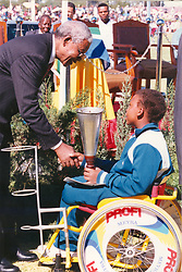 Nelson Mandela talking to a child in a wheelchair. Picture: THE ARGUS.