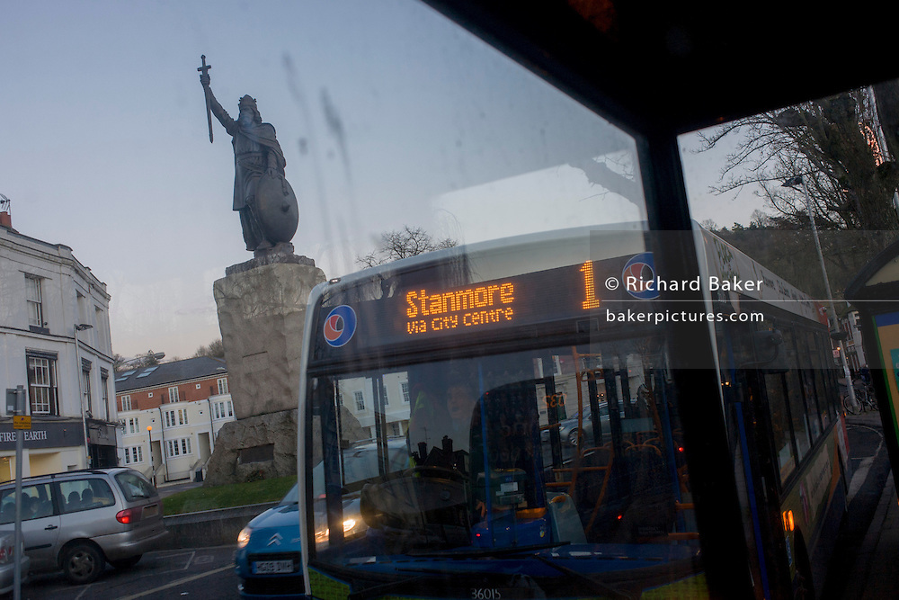 """Towering over a Stagecoach bus service is the statue (by sculptor Hamo Thornycroft) of Saxon King Alfred that overlooks a modern Winchester, Hampshire, England. Alfred the Great (849 - 899) was King of Wessex from 871 to 899. Alfred successfully defended his kingdom against the Viking attempt at conquest, and by his death had become the dominant ruler in England. He is the only English monarch to be accorded the epithet """"the Great"""". The Thornycroft statue was unveiled during the millenary celebrations of Alfred's death."""