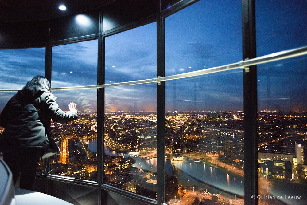 Bezoekster van de Euromast kijkt naar het uitzicht over Rotterdam.
