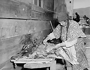 """Y-480418-02. Celilo Falls, Feast of the First Salmon. April 18, 1948. """"Filets. Celilo tribeswoman prepares thick slices of freshly-caught salmon to be served at ceremonial longhouse dinner."""""""