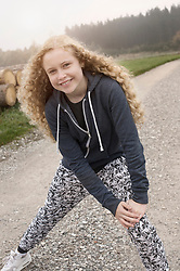 Portrait of a teenage girl stretching her legs on footpath and smiling during dawn, Bavaria, Germany
