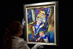 """© Licensed to London News Pictures. 15/06/2017. London, UK. A staff member hangs """"Self-Portrait with my wife Londa and my son Titus"""", 1923, by Conrad Felixmüller (estimate GBP300-500k). Preview of Impressionist and Modern art sale, which will take place at Sotheby's New Bond Street on 21 June.  Photo credit : Stephen Chung/LNP"""