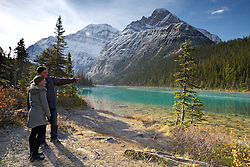 An attractive couple take in the wonders of the Canadian Rockies at Cavell Lake in Jasper National Park