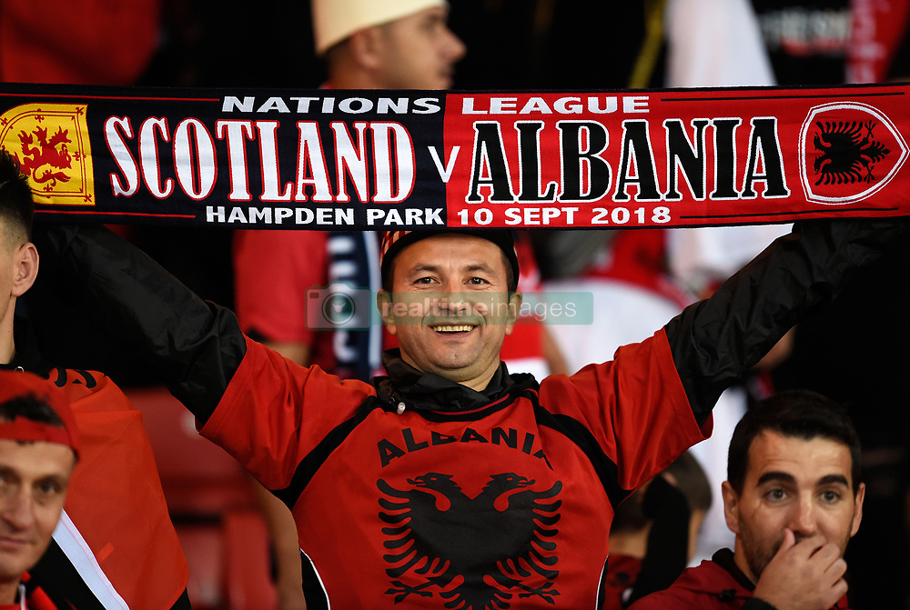 An Albania fan in the stand waves a half and half scarf during the UEFA Nations League, League C Group one match at Hampden park, Glasgow.