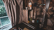 Close up inside a garden shed with old tin cans and packets and a curtain