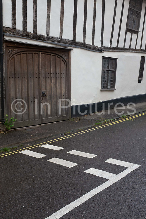 Medieval houses and Give Way traffic lines on the road on Water Lane, wool town, Lavenham, on 9th July 2020, in Lavenham, Suffolk, England. By the late 15th century, the town was among the richest in the British Isles, paying more in taxation than considerably larger towns such as York and Lincoln. Several merchant families emerged, the most successful of which was the Spring family. Heavy traffic is a problem now for small villages dissected by A and B-Roads throughout rural Britain. became a prosperous town based on cloth making. The wool trade was already present by the 13th century, steadily expanding as demand grew. By the 1470s Suffolk produced more cloth than any other county.