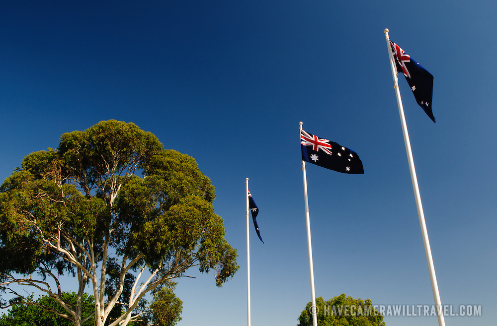 Three Australian Flags and a gum tree against a blue sky at the Australian War Memorial in Canberra, ACT, Australia
