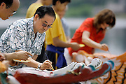 SHOT 7/28/2007 - Jimmy Yip (left) of Denver paints the head of a Dragon Boat during the Dotting of the Eyes ceremony at the 2007 Colorado Dragon Boat Festival. Yip is the Honorary Patron of the Festival. Dragon Boats are awakened, or given life, during the traditional  Dotting of the Eyes ceremony. The sport of Dragon boat racing is over 2000 years old and features teams of 18 paddlers - nine men and nine women plus someone to steer the boat all rowing to the beat of a drum and racing to a flag 200 meters away on Sloan's Lake in Denver, Co. Founded in 2001 to celebrate Denver?s rich Asian Pacific American culture, the Colorado Dragon Boat Festival has become the region?s fastest growing and most acclaimed new festival. Festival-goers get to explore the Asian culture through demonstrations, crafts, shopping, eating, and the growing sport of dragon boat racing. .(Photo by Marc Piscotty / © 2007)