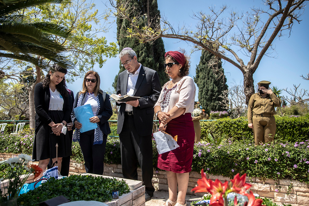 "Volunteers of the ""Stones With Man Heart"" initiative and representatives of the Israeli Ministry of Foreign Affairs recites a prayer next to a grave of a fallen IDF soldier at Kiriyat Schaul Military Cemetery, Ramat Ha Sharon, Israel April 13, 2021. As part of the initiative graves of fallen IDF soldiers who's families are abroad are visited for them. A stone with a writing given by the family abroad is place on the tombstone.Israel will commemorate this year's Memorial  in remembrance of it's soldiers who fell in the line of duty and of  and civilians who where killed in acts of terror. Services and ceremonies were cancelled during 2020 due to the coronavirus pandemic, this year, as vast percentage of the population are vaccinated, ceremonies will be able to take place in a some what ordinary manner."