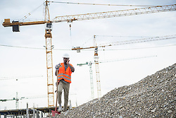 Construction worker holding shovel and talking on smart phone at construction site, Munich, Bavaria, Germany, Europe