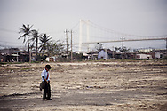 A vietnamese kid pees in the middle of a waste land. Danang, Vietnam, Asia
