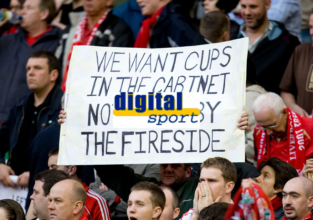 """LIVERPOOL, ENGLAND - Tuesday, April 22, 2008: Liverpool's fans hold up a banner saying """"We want cups in the cabinet, not mugs by the fireside"""" as a reference to a Sky Sports interview with co-owner Tom Hicks, before the UEFA Champions League Semi-Final 1st Leg match against Chelsea at Anfield. (Photo by David Rawcliffe/Propaganda)"""