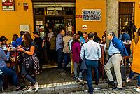 People eating and drinking outside at tapas bar Bodega Santa Cruz, in the Santa Cruz neighborhood of old Seville, Andalusia, Spain.
