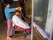 01 NOVEMBER 2014 - YANGON, MYANMAR: A barber gives a customer a haircut in the lobby of an old apartment building in Yangon.    PHOTO BY JACK KURTZ