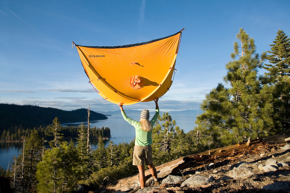 Woman shaking out tent. Lake Tahoe, CA