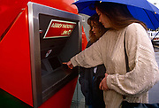 A lady walks away with an open wallet after taking cash from her local London branch of the Abbey National Building Society in 1989. With her finger almost touching the keypad, the lady and her companion are withdrawing cash from this hole in the wall after investing their funds in this branch of Britain's building society. Abbey National plc was a UK-based bank and former building society, which latterly traded under the Abbey brand name. It became a wholly owned subsidiary of the Spanish Santander Group in 2004, and was combined with the savings business of the former Bradford & Bingley in January 2010 to form Santander UK plc. Before the takeover, it was a constituent of the FTSE 100 Index.